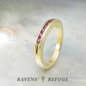 18k yellow gold half eternity band with channel set garnets