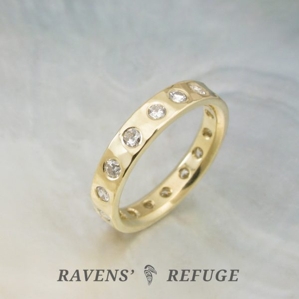 18k gold hammered eternity band with flush set diamonds