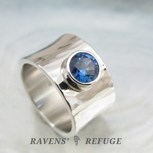 wide platinum engagement ring with bezel sapphire, artisan hand forged
